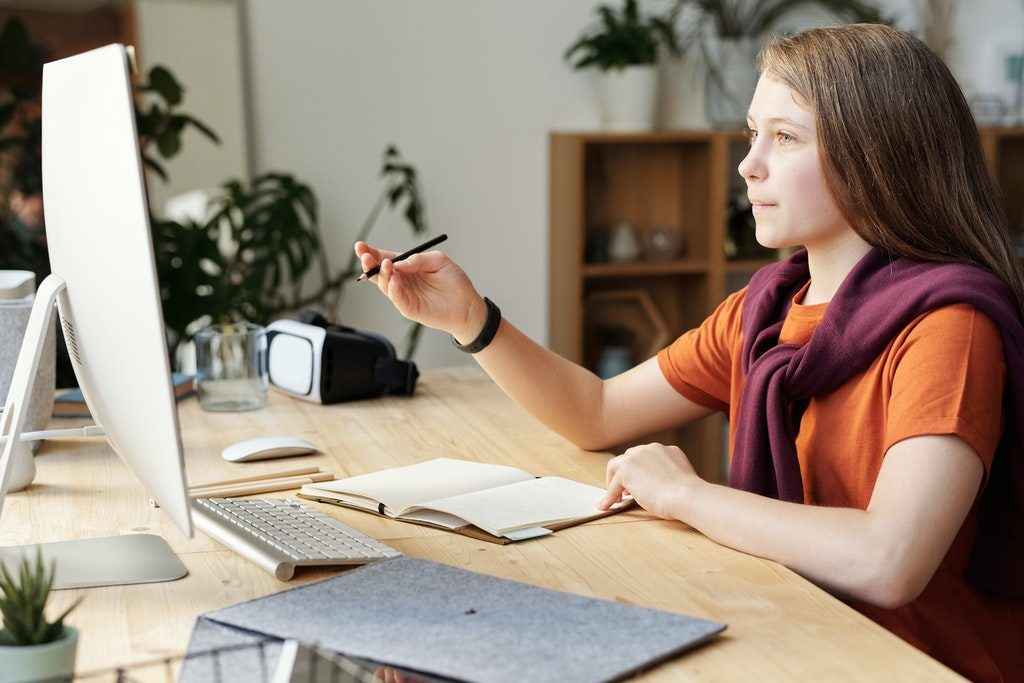 girl-holding-pencil-while-looking-at-imac-4144223